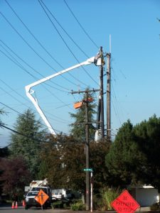 "street filled with power company trucks. extended cherry picker with man working on lines. many power lines and three poles. traffic cones ""be prepared to stop"" sign and caution sign. suburban street and trees."