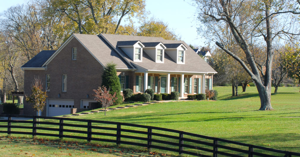 Beautiful elegant home with a rail fence on a large piece of property