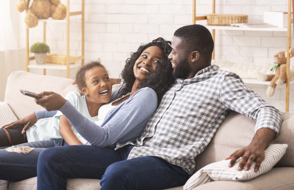 Joyful black family having fun together, relaxing on sofa at home.