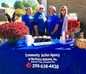 Group of women in front of a table with flowers and drinks. Community Action Agency of Northeast Alabama, Inc. Helping people, changing lives. 256-638-4430