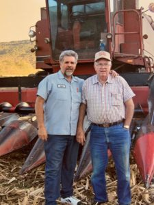 Mike Sisk standing next to his father in front farming equipment.