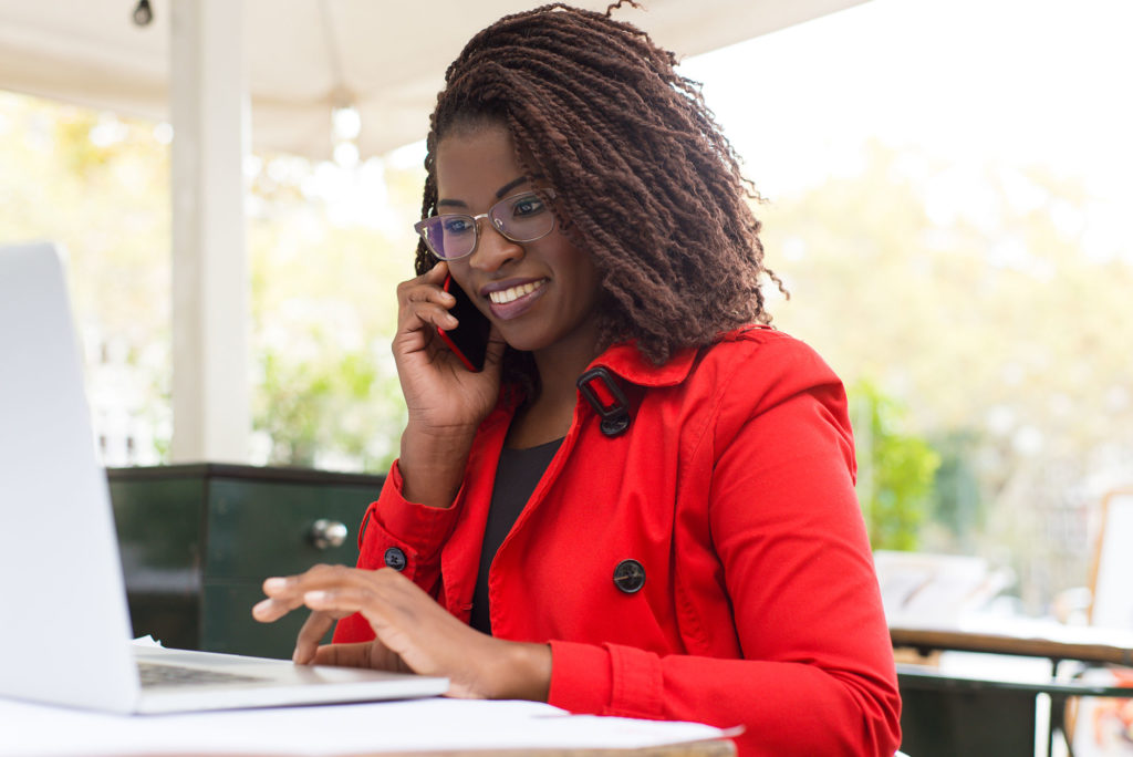 Smiling woman talking on cell phone while on laptop.