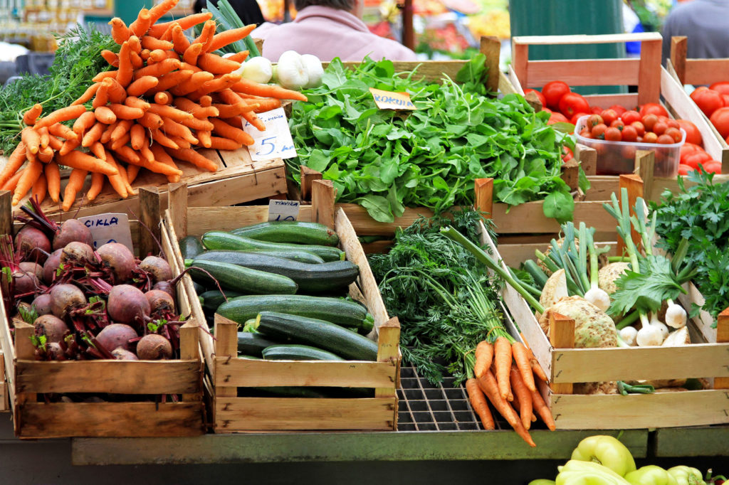 Variety of vegetables in boxes on a stand outside