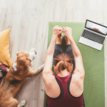 woman doing yoga next to her dog