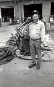 Eugene Talley as a young man holding wire cables