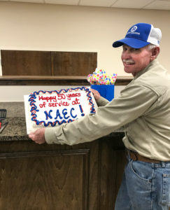 """Eugene Tally holding a cake that has icing saying """"Happy 50 years of service at NAEC"""""""