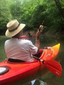 man fishing in canoe on river